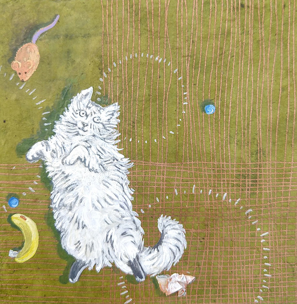 A fluffy white cat lolls on a green rug, surrounded by her toys.